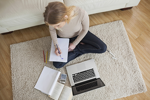 Young woman doing homework and sitting on floor using laptop
